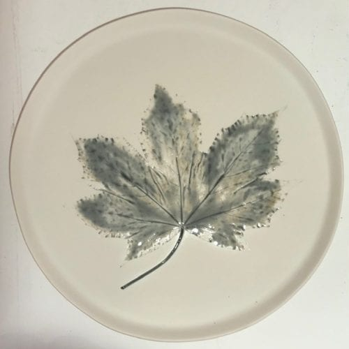 round handmade ceramic dish with leaf detail