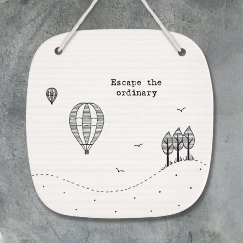 Porcelain hanging plaque with message Escape the ordinary....